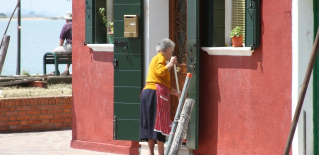 older lady sweeping outside